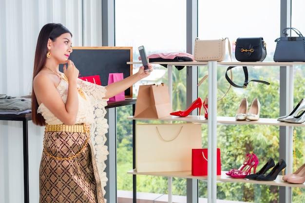 Mooi vrouwenvideogesprek met telefoon in nationaal traditioneel kostuum van thailand bij het shpping van opslag.