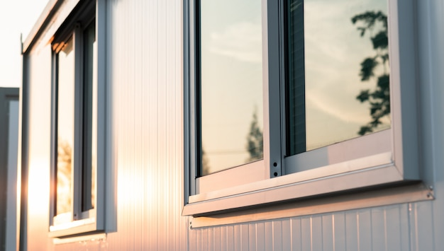 Mooi warm zonsopganglicht die op het venster van het huisglas glanzen met de bezinning van de stadsaard in de ochtend, moderne huis buitenmening