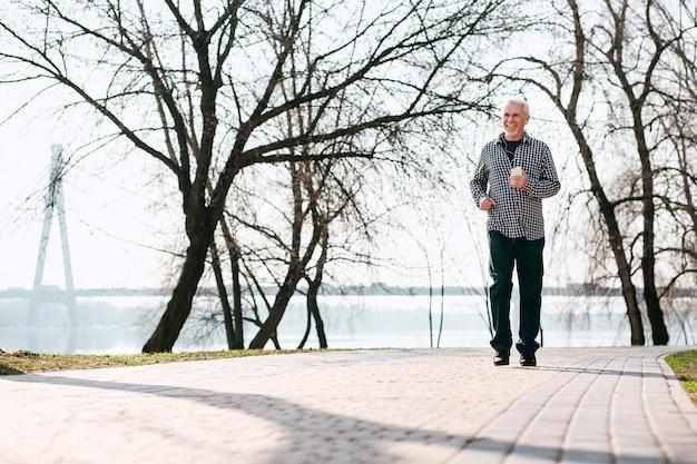 Mooi weer. optimistische senior man loopt en geniet van de natuur