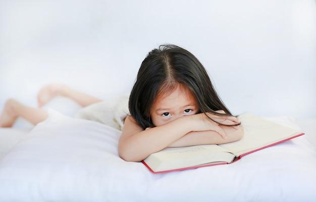 Mooi weinig aziatisch kindmeisje die met hardcoverboek op hoofdkussen op witte achtergrond liggen.
