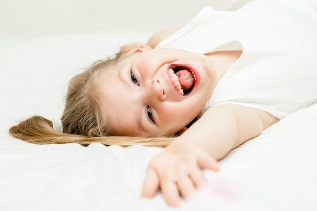 Mooi weinig de zomer witte kleding die van het blondemeisje op de vloer liggen en bij camera op wit glimlachen