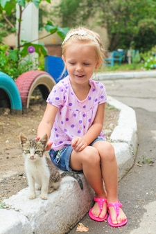 Mooi weinig mooi meisje speelt met een dakloos klein katje