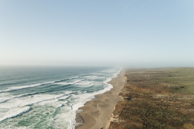 Mooi wijd schot van oceaan dichtbij een woestijn onder een duidelijke blauwe hemel