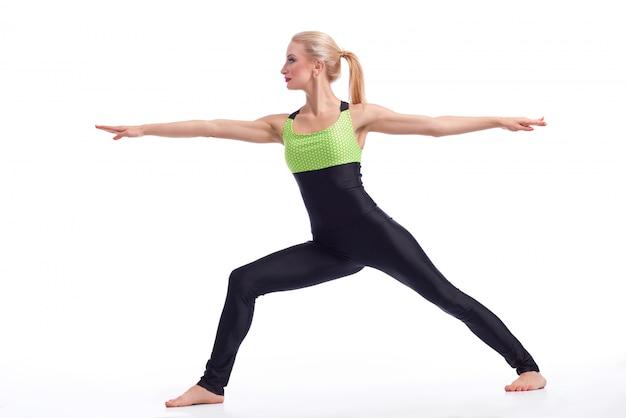Mooi wijfje die het uitoefenen van yoga doen die strijdersasana doen die op wit wordt geïsoleerd