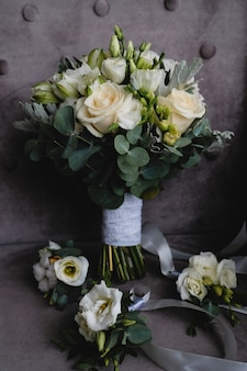 Mooi wit huwelijksboeket en boutonnieres voor bruidsmeisjes.