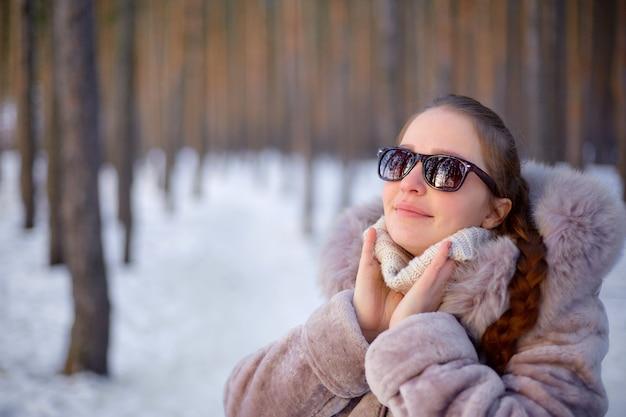 Mooi womanin de winterbos dat een bontjas en zonnebril draagt.