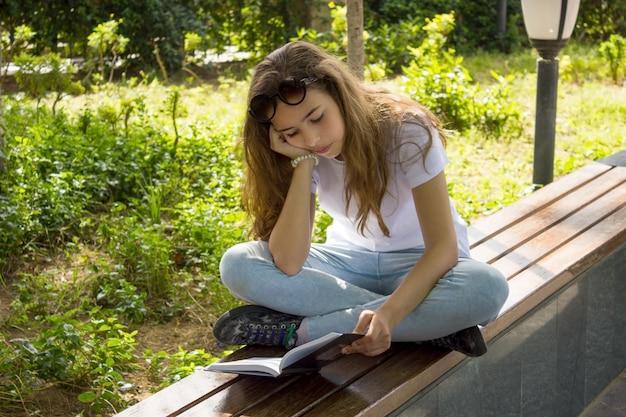 Mooi yaoung meisje dat een boek op een bank in een park leest