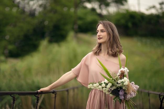 Mooi zacht meisje in een perzikkleurige jurk lopen op een brug met een boeket bloemen