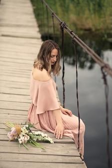 Mooi zacht meisje in een perzikkleurige jurk zittend op een landelijke houten brug met een boeket bloemen