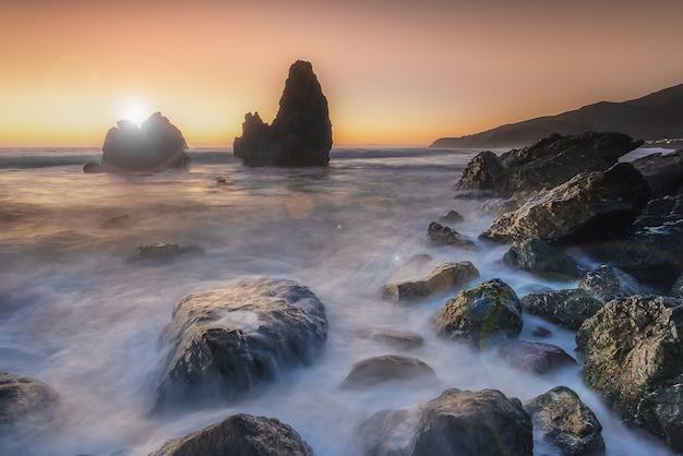 Mooi zeegezicht van het westenkust op vreedzame oceaan tijdens zonsondergang
