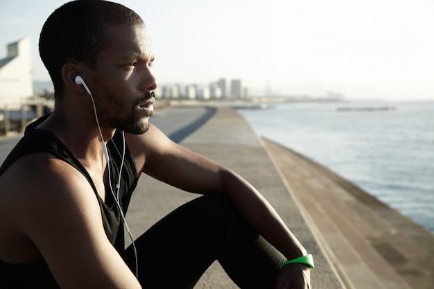Mooi zijwaarts schot van jonge afro-amerikaanse man op zoek voor hem en overweegt water en zonsondergang.
