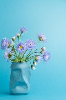 Mooi zomers lenteboeket van paarse madeliefjes bloemen in een blikje frisdrank in plaats van een vaas.