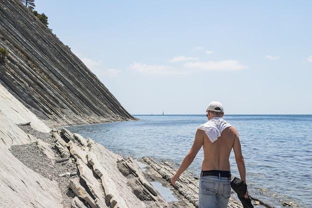 Mooi zomers zeegezicht. een man loopt langs een groot stenen wild strand. omgeving van de badplaats gelendzhik. rusland, kust van de zwarte zee