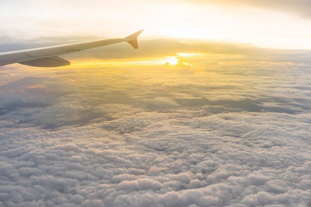 Mooi zonlicht en bewolkt zoals gezien door venster van een vliegtuig