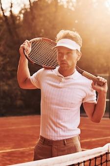 Mooi zonlicht. jonge tennisser in sportieve kleding is buiten op het veld.