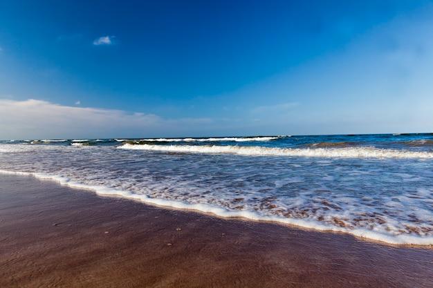 Mooi zonnig weer aan de baltische zeekust, koud zomerweer aan de baltische zeekust, zeegezicht aan de zee op een zonnige dag met blauwe lucht en veel golven op het water