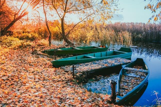 Mooi zonsonderganglandschap met boten bij de rivieroever