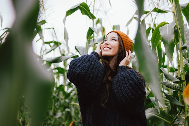 Mooi zorgeloos lang haar aziatisch meisje in gele hoed en gebreide trui in herfst maïsveld