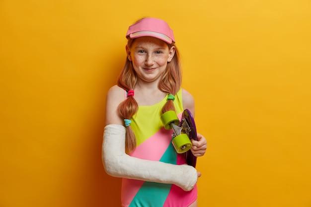 Mooi zorgeloos meisje met twee paardenstaarten, blij na het rijden op een skateboard, draagt een cast op een gebroken arm, gekleed in een badpak en een pet, brengt vrije tijd door in het skatepark, geïsoleerd op een gele muur