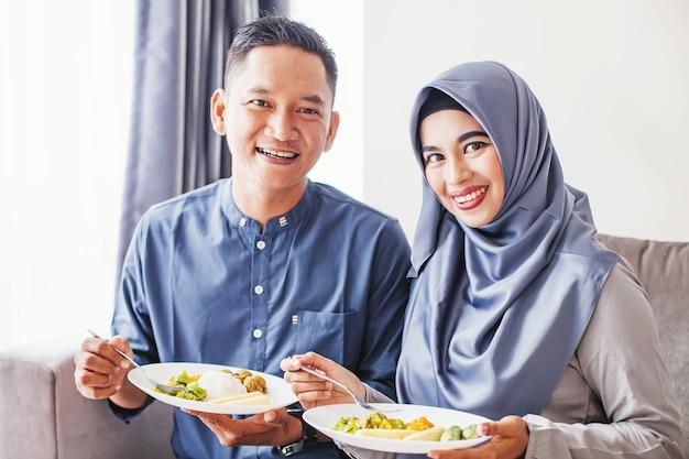 Mooi zuidoost-aziatisch paar dat feestelijke maaltijd eet op eid-viering