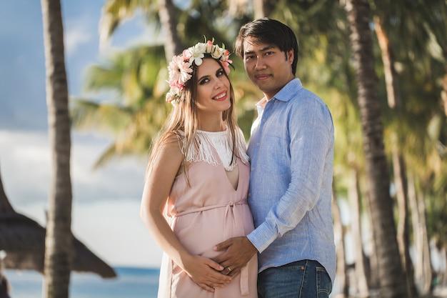 Mooi zwanger meisje en man op het strand