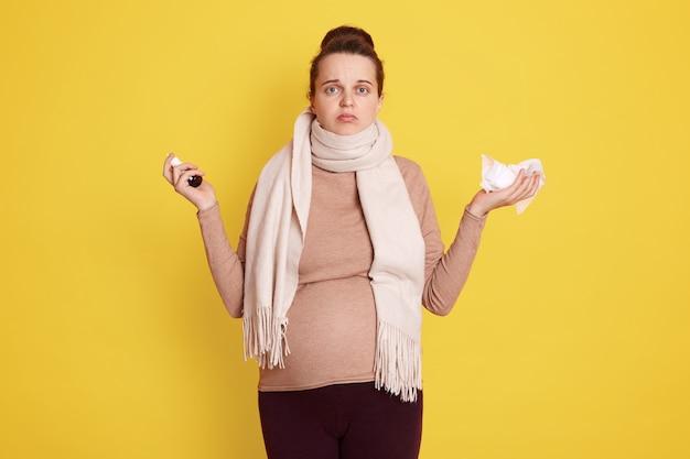 Mooi zwanger meisje in beige trui en sjaal gebruikt remedie voor verstopte neus, boos aanstaande moeder met hulpeloze blik poseren geïsoleerd over gele muur.