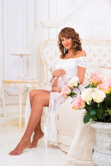 Mooi zwanger meisje in een witte kanten jurk zit op een bed van rozen