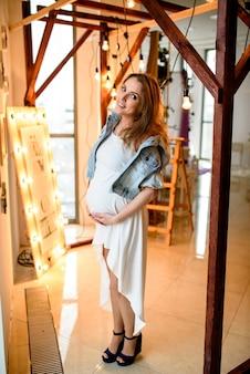 Mooi zwanger meisje in het witte kleding glimlachen