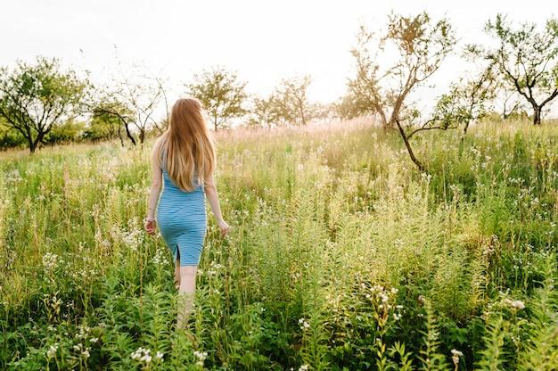 Mooi zwanger meisje in stijlvolle zomerjurk wandelen in veld met bloemen in zonlicht, genieten van vrijheid gevoel