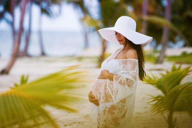 Mooi zwanger meisje in witte jurk en hoed met brede rand op het strand in de buurt van palmbomen