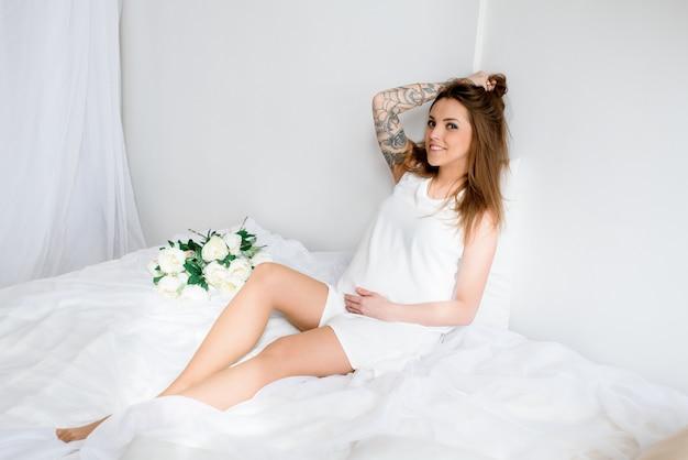 Mooi zwanger meisje met parasol in een witte jurk.