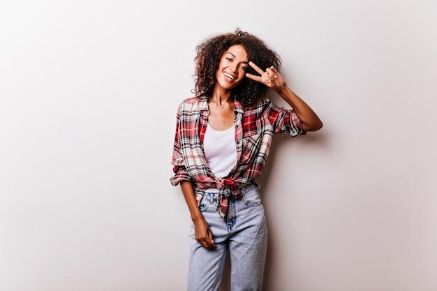 Mooi zwart meisje in vintage denim broek poseren met vredesteken. enthousiast vrouwelijk model in geruit overhemd dat op wit wordt geïsoleerd.