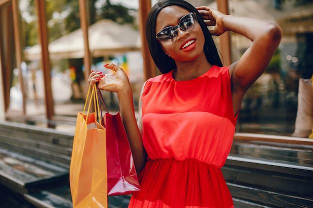 Mooi zwart meisje met boodschappentassen in een stad
