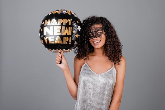 Mooi zwart meisje met gelukkige nieuwe jaarballon die maskerademasker draagt dat over grijs wordt geïsoleerd