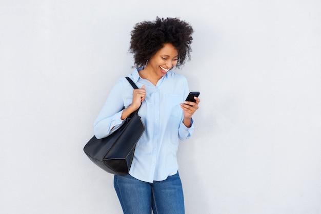 Mooi zwarte met beurs die cellphone en het lachen bekijkt