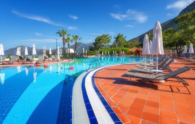 Mooi zwembad met ligbedden en parasols bij zonsopgang in de zomer. luxe resort. liberty hotels lykië. ollüdeniz, turkije. landschap met leeg zwembad, ligstoelen, groene bomen, bergen, blauwe lucht