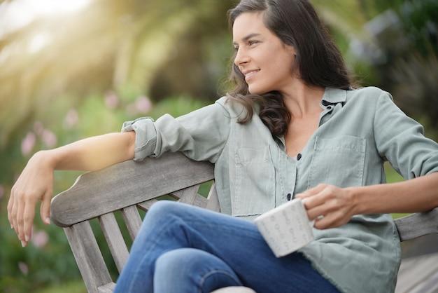 Mooie 40-jarige vrouw die ontspant in de tuin