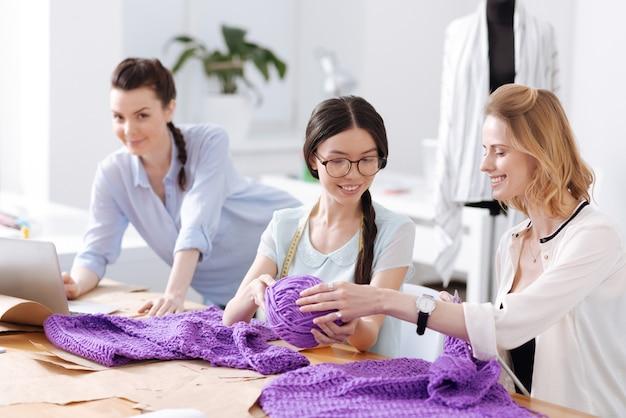 Mooie aangename kleermaker die een grote bal paarse draden doorgeeft aan haar glimlachende collega terwijl de andere werknemer naar voren kijkt en glimlacht
