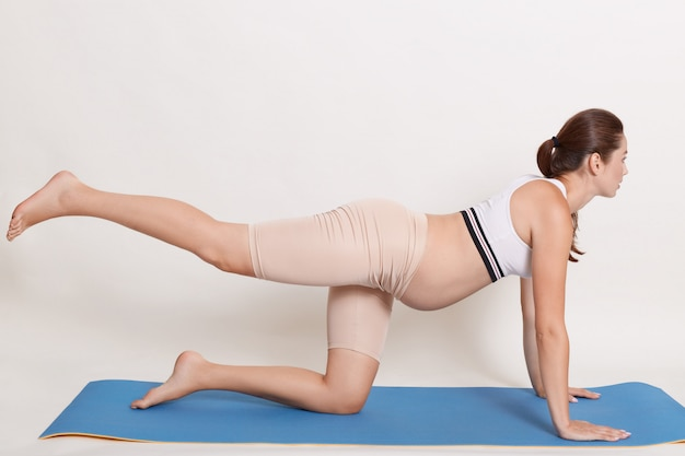 Mooie aanstaande moeder die yoga thuis doet