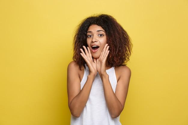 Mooie aantrekkelijke afrikaanse amerikaanse vrouw met trendy glazen posten over gele studio achtergrond. ruimte kopiëren.