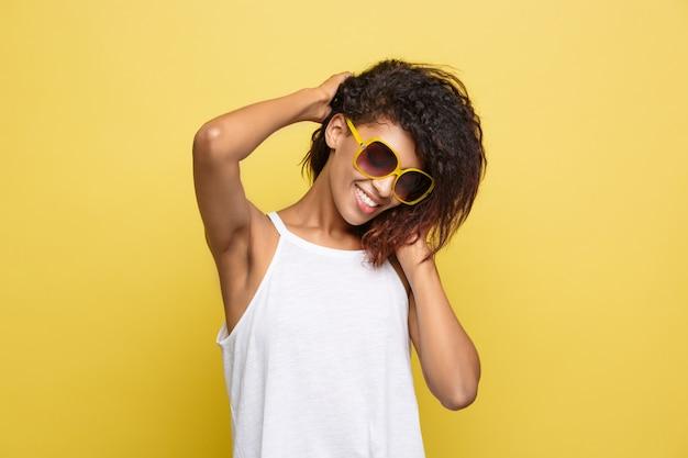 Mooie aantrekkelijke afro-amerikaanse vrouwspelen met haar krullend afro haar. gele studio achtergrond. ruimte kopiëren.