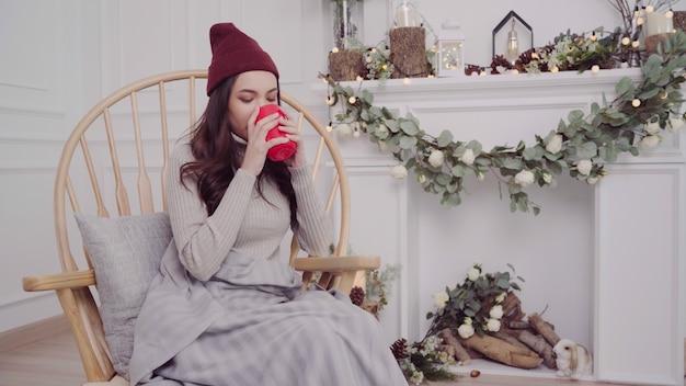 Mooie aantrekkelijke aziatische vrouw die een warme kop van koffie of thee houdt terwijl het liggen op stoel
