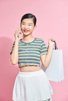 Mooie aantrekkelijke aziatische vrouw met boodschappentassen en bellen met mobiele telefoon geïsoleerd op roze