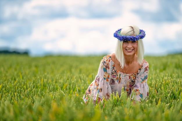 Mooie, aantrekkelijke, blonde vrouw met korenbloem blauwe kroon op het gebied van granen.