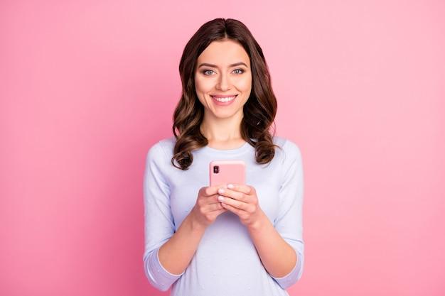 Mooie aantrekkelijke dame houdt telefoon vast en typt een brede glimlach