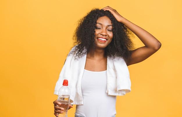 Mooie aantrekkelijke jonge bezwete afro-amerikaanse drinkwater na een training