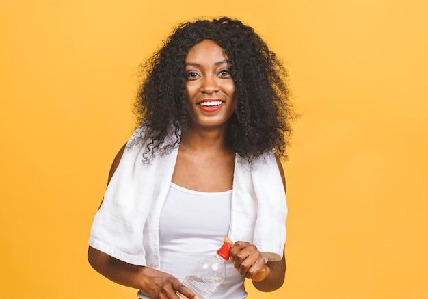 Mooie aantrekkelijke jonge bezwete afro-amerikaanse zwarte vrouw drinkwater na training