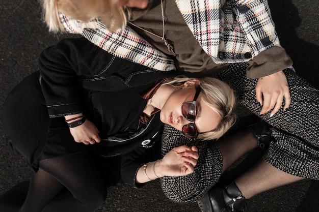 Mooie aantrekkelijke jonge blonde vrouw in trendy zonnebril in mode zwarte jeugdkleren rustend op vriendin in stad Premium Foto