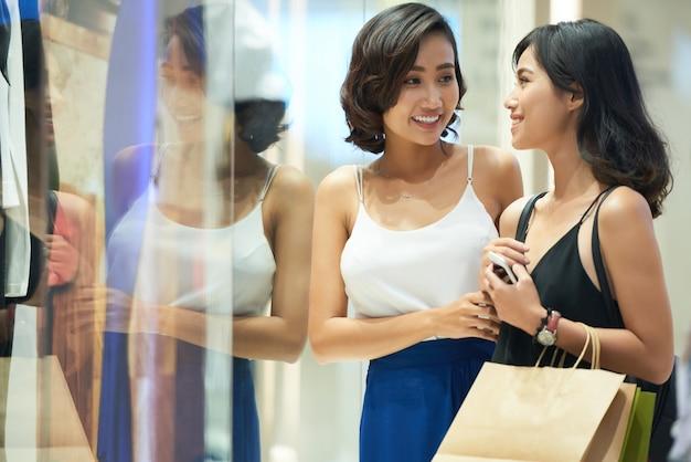 Mooie aantrekkelijke jonge vrouw die in het winkelcentrum loopt met veel boodschappentassen en nieuwe kleding en schoenen koopt