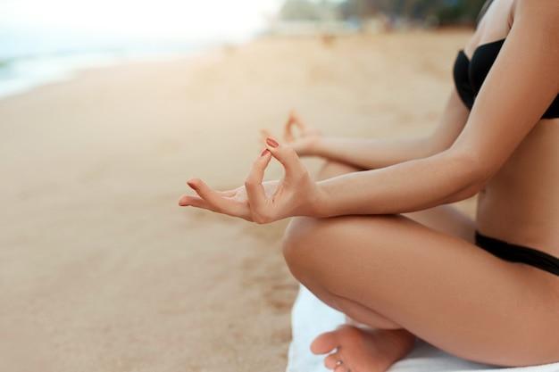 Mooie aantrekkelijke jonge vrouw die 's ochtends yoga op het strand uitoefent. meisje beoefent yoga. fitness vrouw